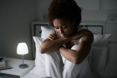 Depressed woman in her bed. Sad depressed woman sitting in her bed late at night, she is pensive and suffering from insomnia Stock Image