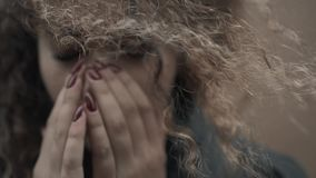 Depressed woman holding face in hands, young crying girl student close up, emotional portrait with tears. Depressed woman holding face in hands royalty free stock image