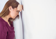 Depressed woman leaning her head against a wall Royalty Free Stock Photos