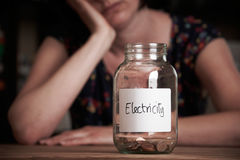 Depressed Woman Looking At Jar Labelled Electricity Stock Image