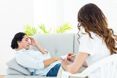 Depressed woman lying on the couch while her therapist taking notes Royalty Free Stock Image