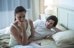 Depressed Woman With Man In Background On Bed Stock Photos
