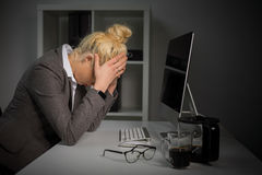 Depressed woman at the office holding her head Royalty Free Stock Photos