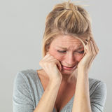 Depressed woman in pain expressing regret and sadness. Drama concept - depressed young blond woman in pain with big tears expressing her regret and sadness, grey royalty free stock images