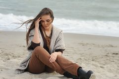 Fashion pensive woman portrait alone on a sea beach. Depressed woman portrait sitting alone on a sea beach Royalty Free Stock Images