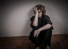 Depressed woman. Depressed and sad woman sitting on the floor in the empty room. Low key stock images