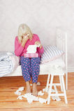 Depressed woman sitting bed. Female with pink pajama and tissues sitting on bed in desperation Stock Image
