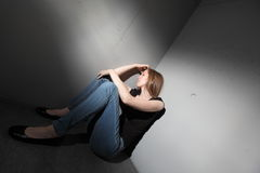 Depressed woman. Sitting in the corner (color toned image Royalty Free Stock Photography