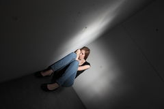 Depressed woman. Sitting in the corner (color toned image royalty free stock photo