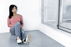 Depressed woman sitting on the floor. Depressed black woman sitting against wall looking out window Royalty Free Stock Image