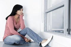 Depressed woman sitting on floor. Depressed black woman sitting against wall on floor looking out window Royalty Free Stock Photos