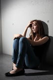 Depressed woman. Sitting on the floor (color toned image royalty free stock photography