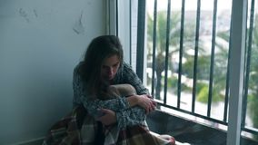 Depressed woman crying by the window with rain. Depressed woman sitting on the floor by the window with the rain falling outside. Lonely woman in despair with stock video