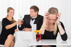 Depressed Woman Sitting In Restaurant. In Front Of Couple Toasting Glass Of Cocktails Stock Photography