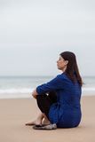 Depressed woman sitting on the sand of a beach Royalty Free Stock Image
