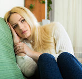 Depressed woman sitting in silence. Depressed young woman sitting in silence and thinking about her problems Royalty Free Stock Photography