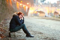 Depressed woman sitting by the waterside in a city nearby a bridge crying and feeling lonely. Depressed young woman sitting by the waterside near a bridge crying Stock Photography