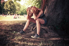 Depressed woman sittng under a tree Royalty Free Stock Photo