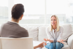 Depressed woman speaking to a therapist. Depressed women speaking to a therapist while she is taking notes Royalty Free Stock Image