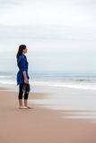 Depressed woman watching the sea in a deserted beach Stock Image