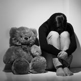 Depressed women. Black and white image of young depressed woman sitting on the floor near teddy bear and hiding her face behind knees Royalty Free Stock Photography