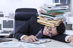 Depressed worker with documents. Caucasian businessperson sleeping in the office with documents on his head, shot in the office Stock Photo