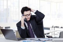 Depressed worker speaking on the phone Stock Photos