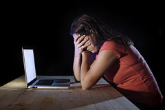 Depressed worker or student woman working with computer alone late night in stress Stock Images