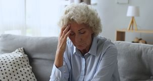 Depressed worried old woman feeling headache or mental stress concept