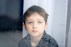 Depressed 7 years boy child looking out the window. Royalty Free Stock Photo