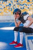 depressed young american football player sitting