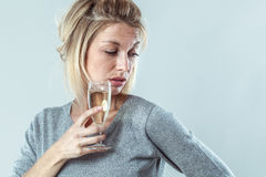 Depressed young blond woman drinking glass of wine. Female drinker - depressed young blond woman drinking a glass of wine suffering from booze nausea and royalty free stock photo