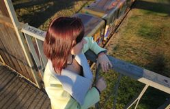 Depressed young girl thinks about suicide on the old rustic broken bridge. Concept stop teen suicide. View from the back royalty free stock photos