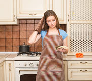 Depressed young housewife in apron and oven gloves with money in Stock Images