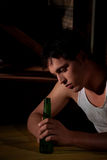 Depressed young man with beer bottle Stock Image