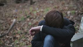 Depressed young man crying alone in park, having hysterics over troubles in life stock footage