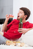 Depressed young man eating sweets Stock Images