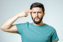 Depressed young man shooting to his head. Isolated on gray Stock Images