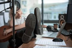 Feet on desk of male guitarist feeling melancholy. Depressed young man is sitting in his sound recording studio with guitar. Focus on his legs shoes on table Royalty Free Stock Photos