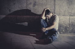 Depressed young man sitting on street ground with shadow on concrete wall Royalty Free Stock Images