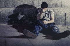 Depressed young man sitting on street ground with shadow on concrete wall Royalty Free Stock Photography