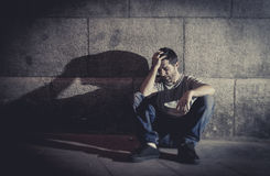 Depressed young man sitting on street ground with shadow on concrete wall Stock Photos