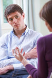 Depressed Young Man Talking To Counsellor. Depressed Young Man Talking To Female Counsellor stock photos