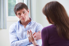 Depressed Young Man Talking To Counsellor. Depressed Young Man Talks To Counsellor stock image