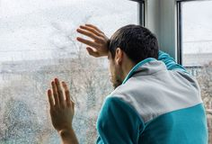 Depressed young man upset with bad news looking through rainy window glass. Stock footage Stock Photography