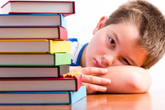 Depressed young schoolboy eyeing his textbooks. Depressed young schoolboy is eying his textbooks piled in a huge stack alongside him as he rests his head o the royalty free stock photo
