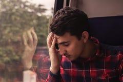 Sad upset man traveling by train. Depressed young student man traveling home by train.Sad upset man traveling by train royalty free stock image