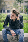 Depressed Young White Man Sitting at Street Side Stock Image
