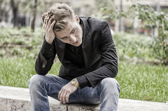 Depressed Young White Man Sitting at Street Side Royalty Free Stock Photos