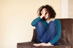 Depressed young woman. A depressed young woman is sitting barefoot on an armchair Stock Image